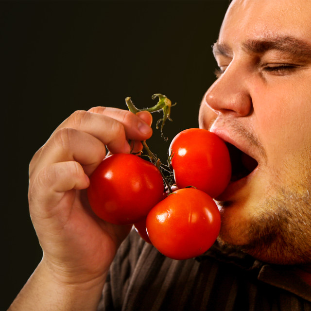 """Diet fat man eating healthy food . Healthy breakfast with vegetables."" stock image"