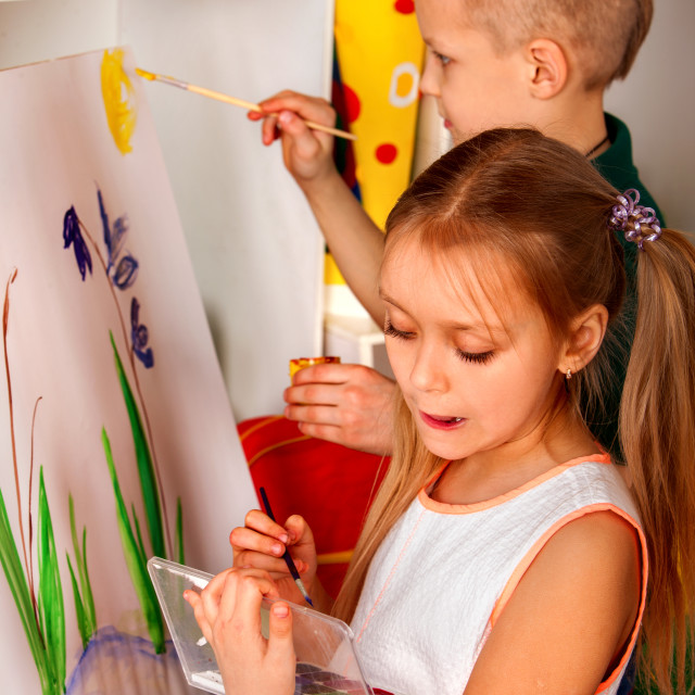 """""""Children painting finger on easel. Group of kids alone in class school."""" stock image"""