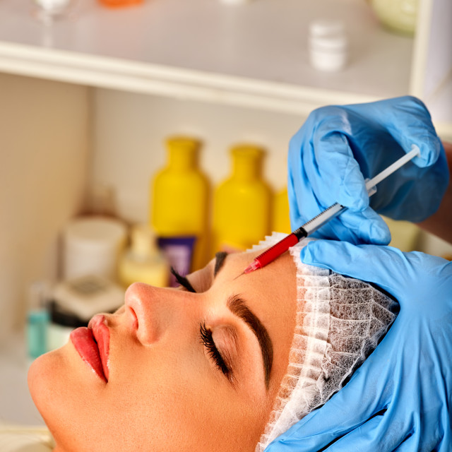 """Filler injection for woman forehead face. Plastic aesthetic facial surgery ."" stock image"