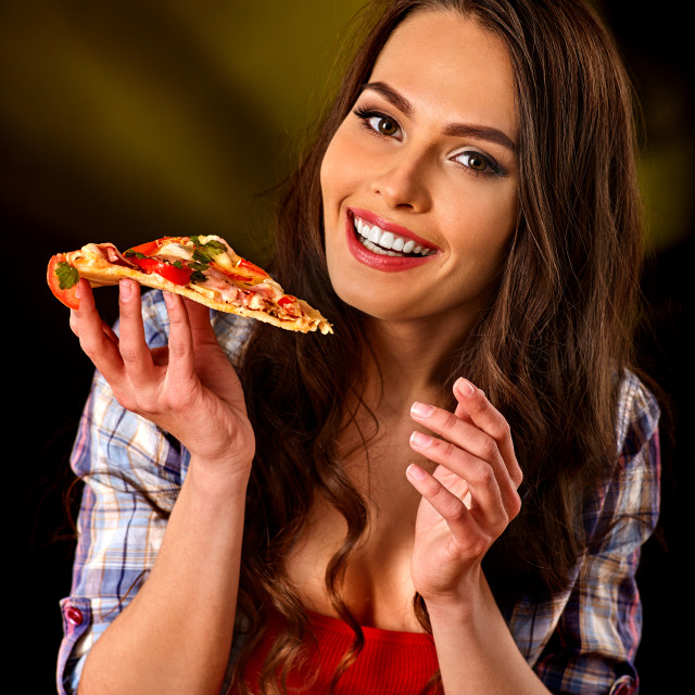 """Woman eating slice of Italian pizza. Student consume fast food."" stock image"