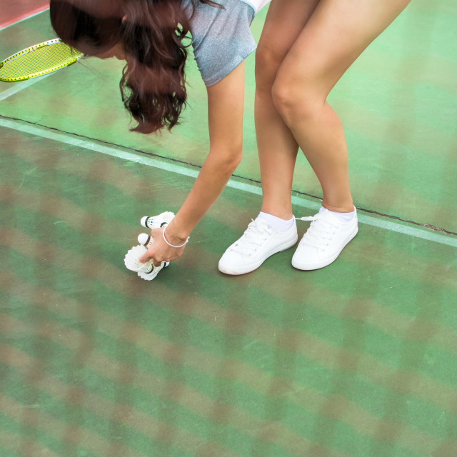 """Girl collecting badminton ball the net"" stock image"