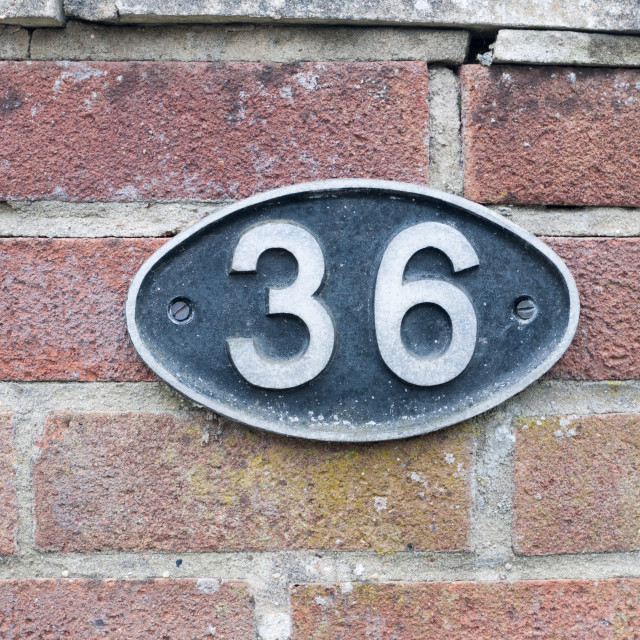 """a number plate on a brick wall with 36 on it"" stock image"