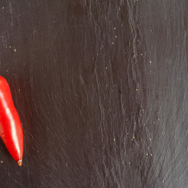 """Red chilli pepper on a slate chopping board"" stock image"