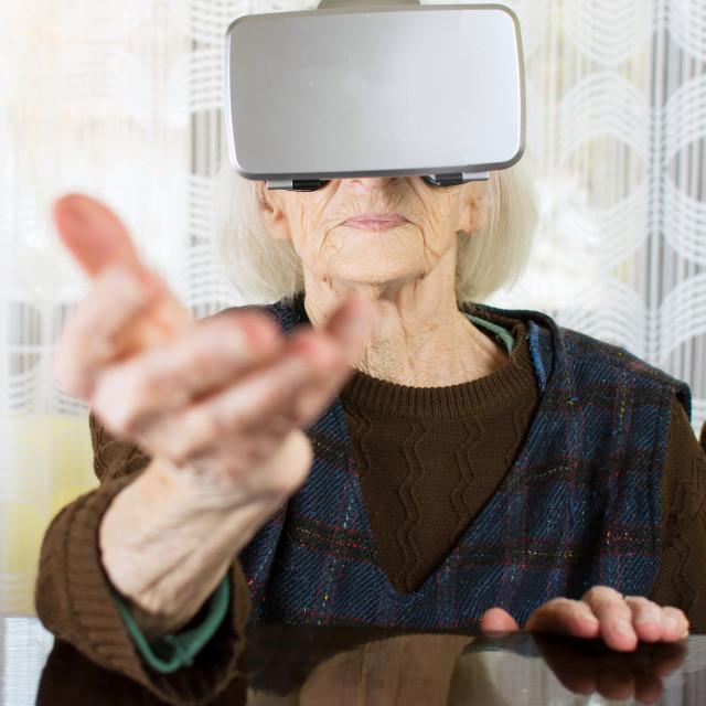 """Grandma using virtual reality goggles"" stock image"