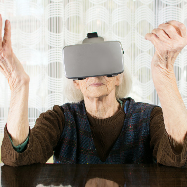 """Senior woman using virtual reality goggles"" stock image"