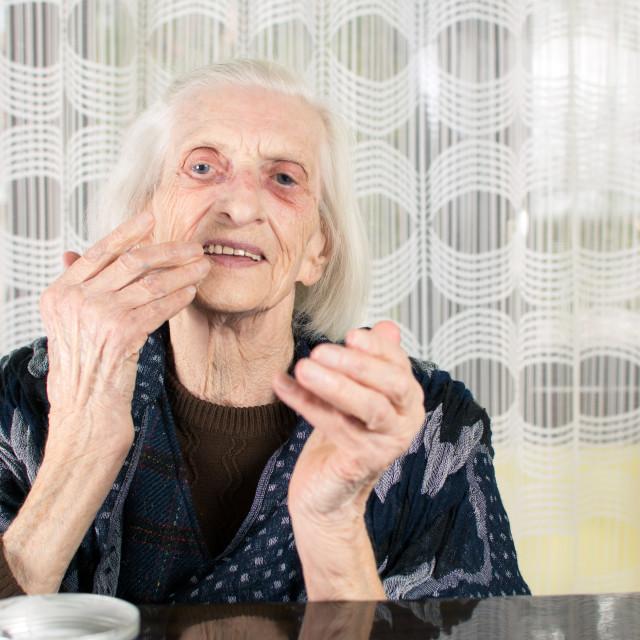 """Senior woman applying face cream"" stock image"