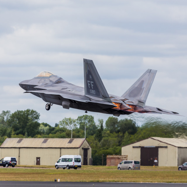 """F-22 Raptor roaring into the sky"" stock image"
