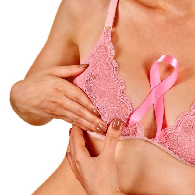 """""""Pink badge on woman hand to support breast cancer cause."""" stock image"""