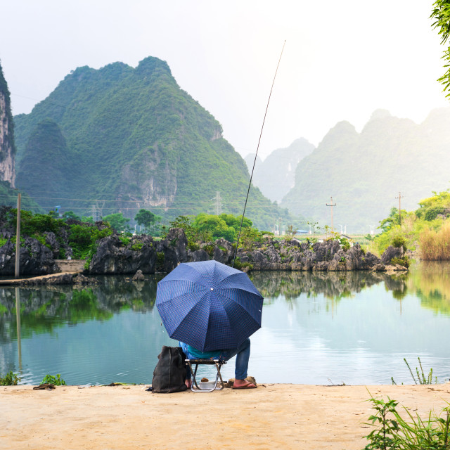 """Lonely fisherman in a scenic lake of Guangxi province, China"" stock image"
