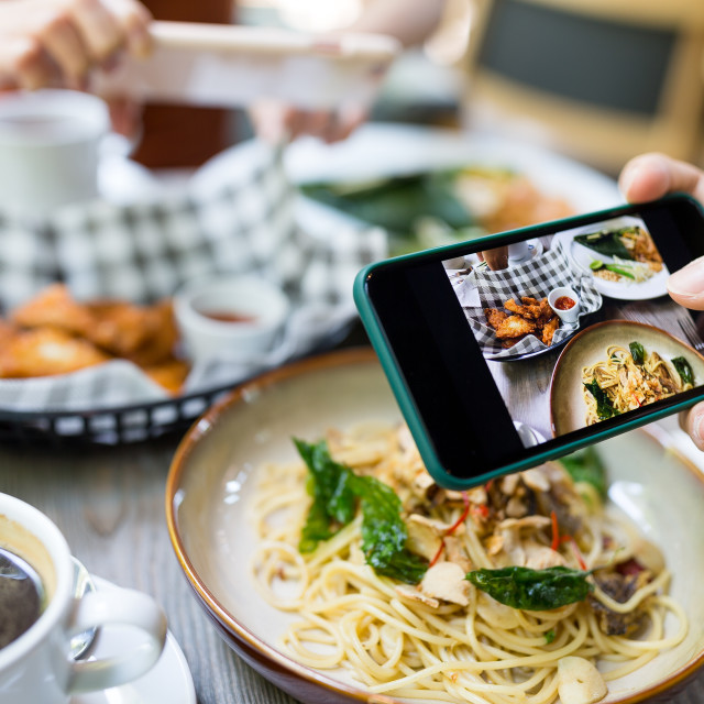 """""""Friends taking photo on cellphone in restaurant"""" stock image"""