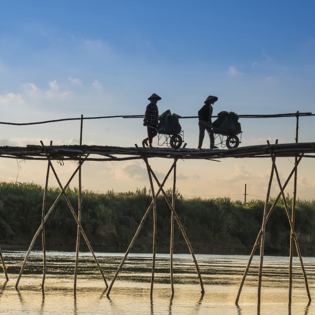 """Farmers go to work on a bridge made of bamboo at Cam Dong village, Quang Nam province, Vietnam"" stock image"
