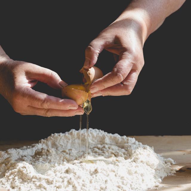 """""""Senior woman kneads pastry, adding egg to flour"""" stock image"""