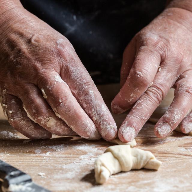 """Senior woman, grandma, rolling fresh homemade croissants"" stock image"