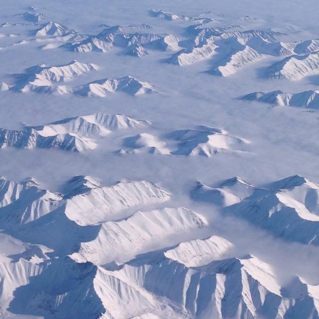 """Mountaintops cutting through clouds"" stock image"