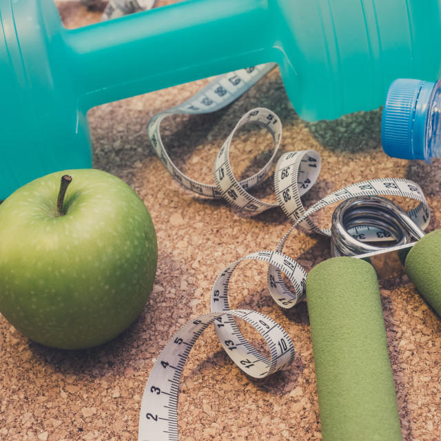 """Lay Flat - Dumbbell, Fresh Apple, Measuring Tape, Mineral Water,"" stock image"