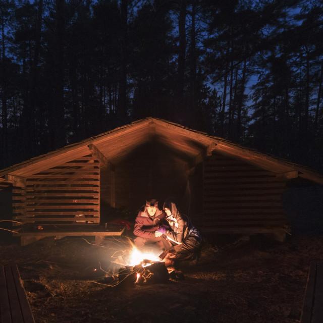 """Couple enjoying a warm campfire at night"" stock image"