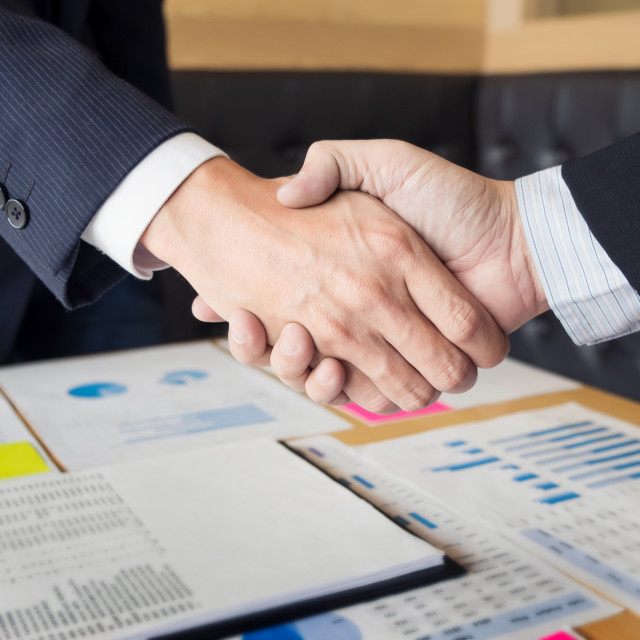 """""""Two confident business man shaking hands during a meeting in the"""" stock image"""