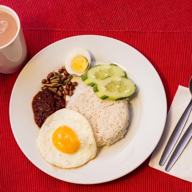 """Malaysian Food - Nasi Lemak and Frothy Teh Tarik on a red backgr"" stock image"