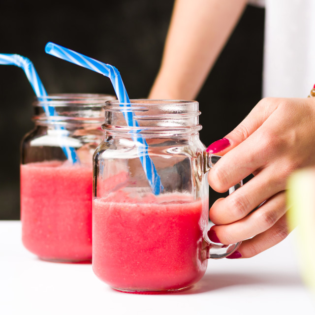 """""""Female holding watermelon smoothies in jars"""" stock image"""