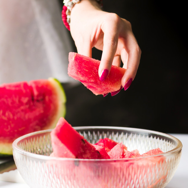 """Woman taking watermelon slice from a bowl"" stock image"