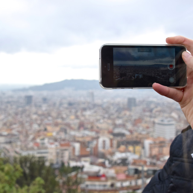 """Woman records a video overlooking a large city"" stock image"