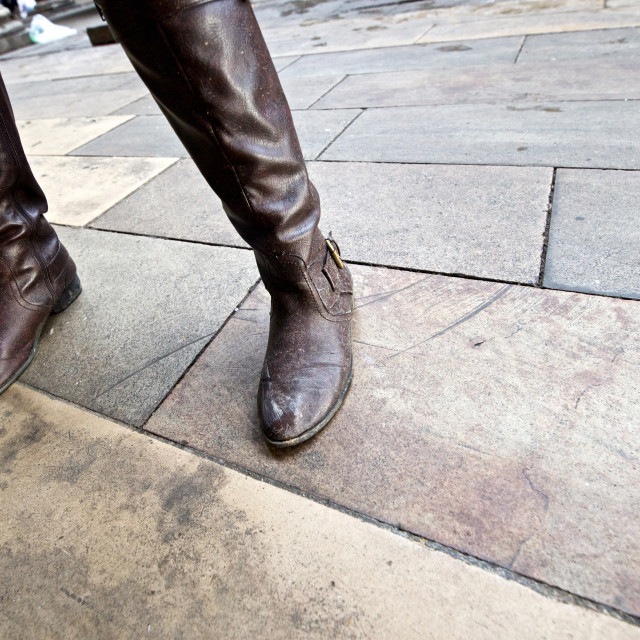"""Angled close up of woman's legs and dirty boots"" stock image"