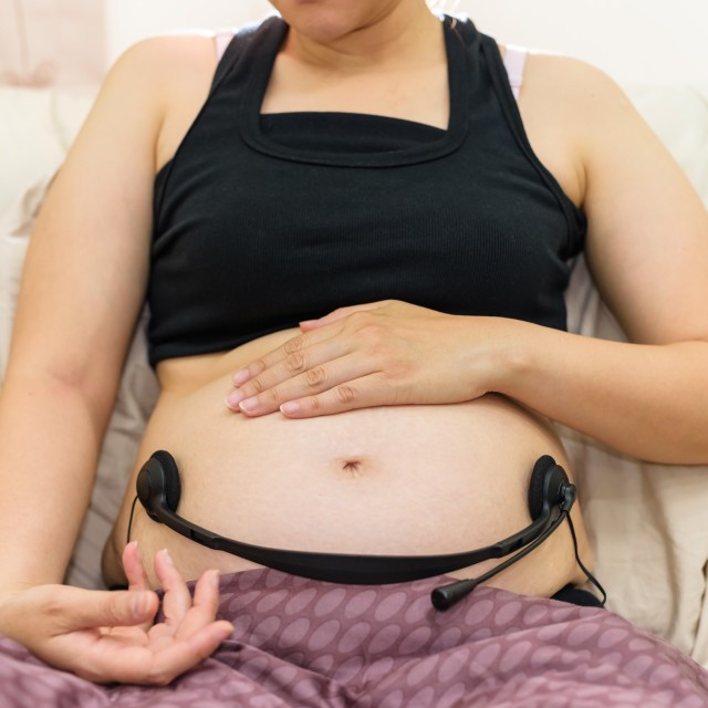 """""""pregnant holding headphones on belly"""" stock image"""