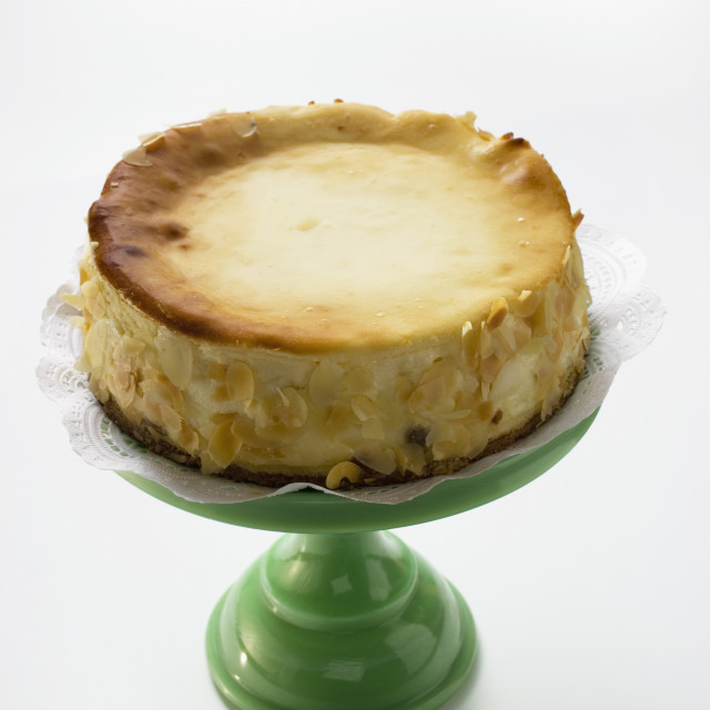"""Cheesecake with flaked almonds on cake stand"" stock image"