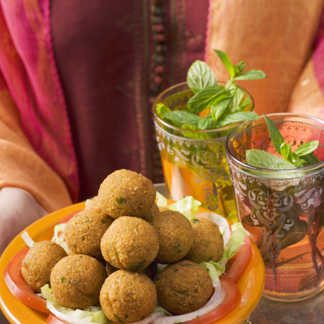 """Woman holding tray of falafel (chick-pea balls) and tea"" stock image"