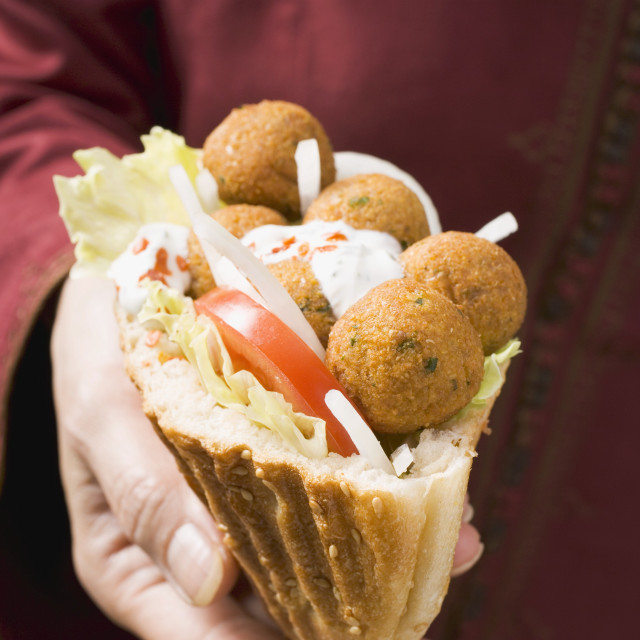 """Woman holding flatbread filled with falafel (chick-pea balls)"" stock image"