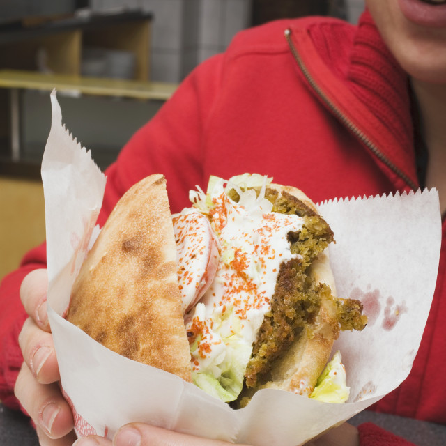 """Person holding pita bread filled with falafel in snack bar"" stock image"