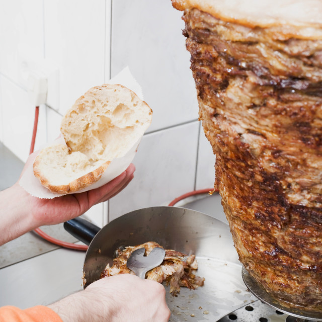 """""""Making a döner kebab: filling pita bread with meat"""" stock image"""