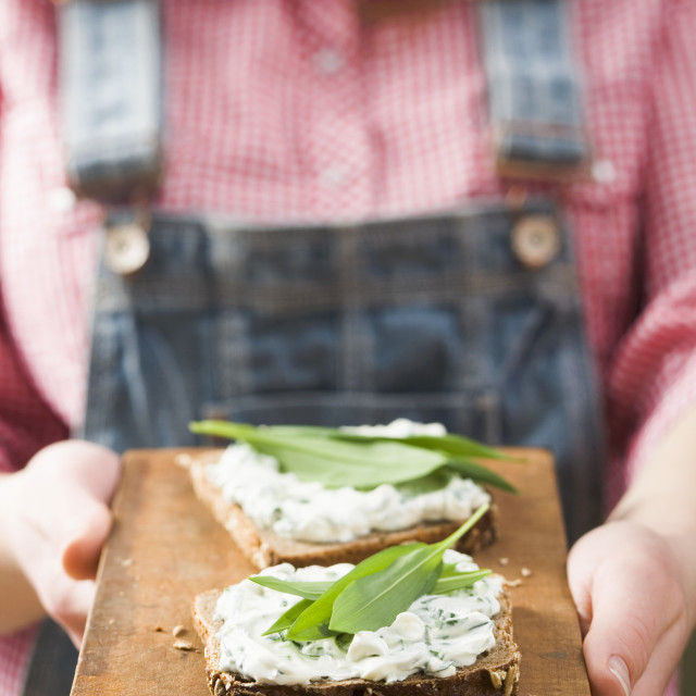 """""""Person holding wholemeal bread with quark & ramsons on board"""" stock image"""