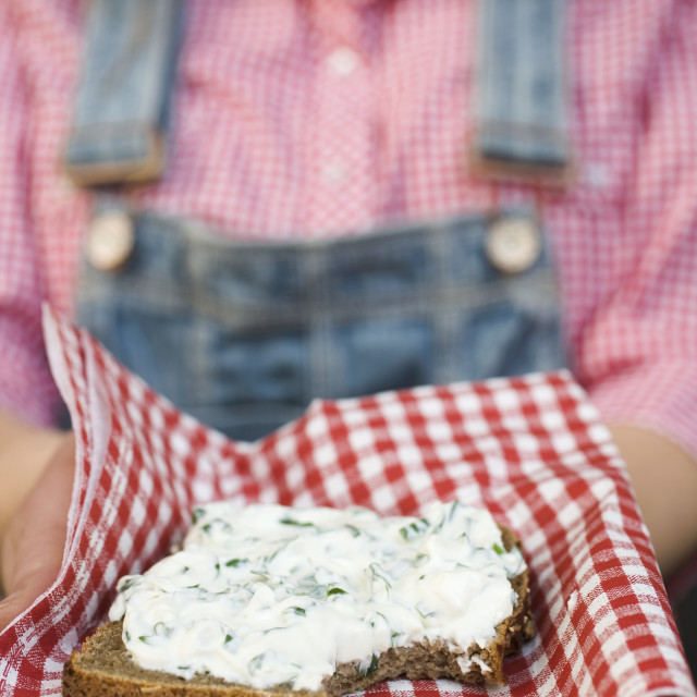 """""""Woman holding wholemeal bread with quark & ramsons on napkin"""" stock image"""