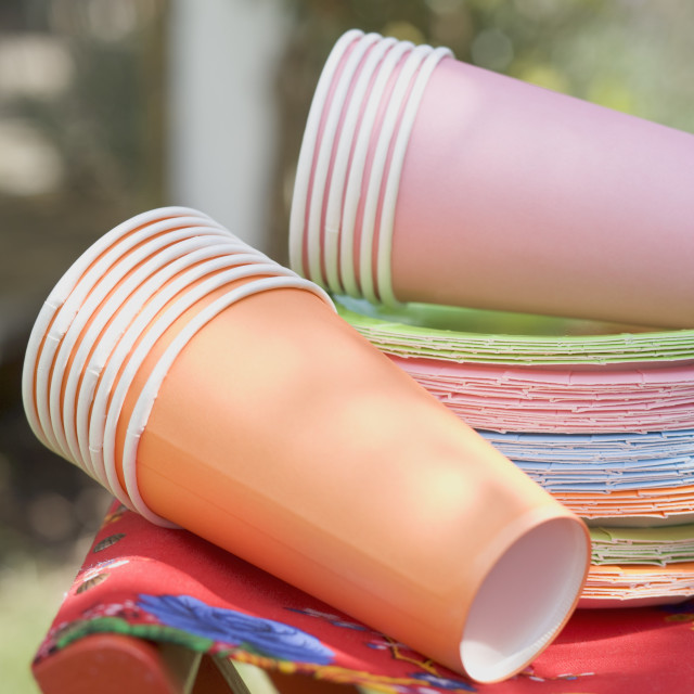 """""""Coloured paper cups and plates on folding stool in garden"""" stock image"""