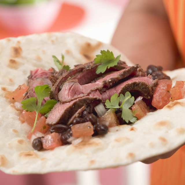 """Woman holding fajita with beef, beans and tomatoes"" stock image"