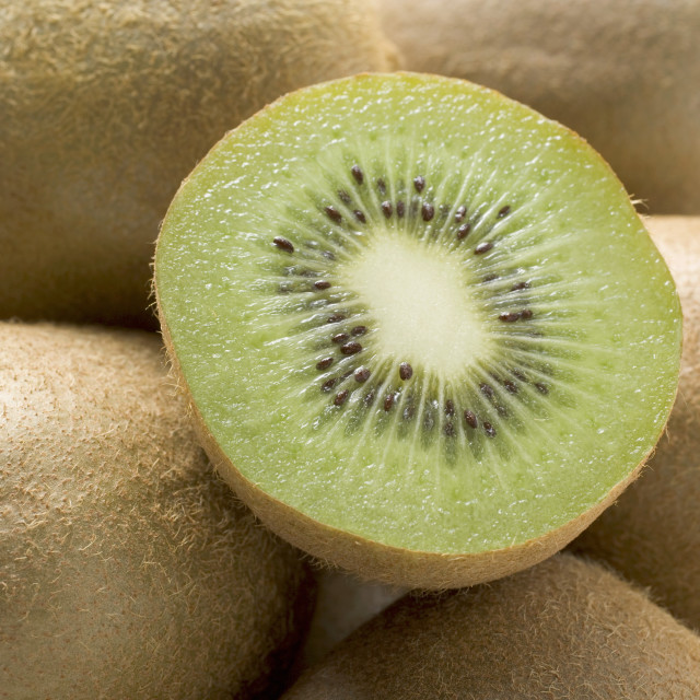 """Half a kiwi fruit on several whole kiwi fruits (close-up)"" stock image"