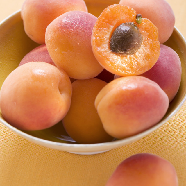 """""""Whole apricots and half an apricot in yellow bowl"""" stock image"""