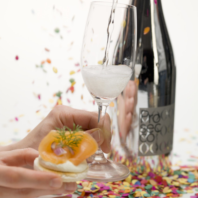 """Hands holding cracker with smoked salmon & glass of Prosecco"" stock image"