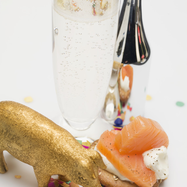 """Glass of Prosecco, salmon appetiser, lucky pig & confetti"" stock image"