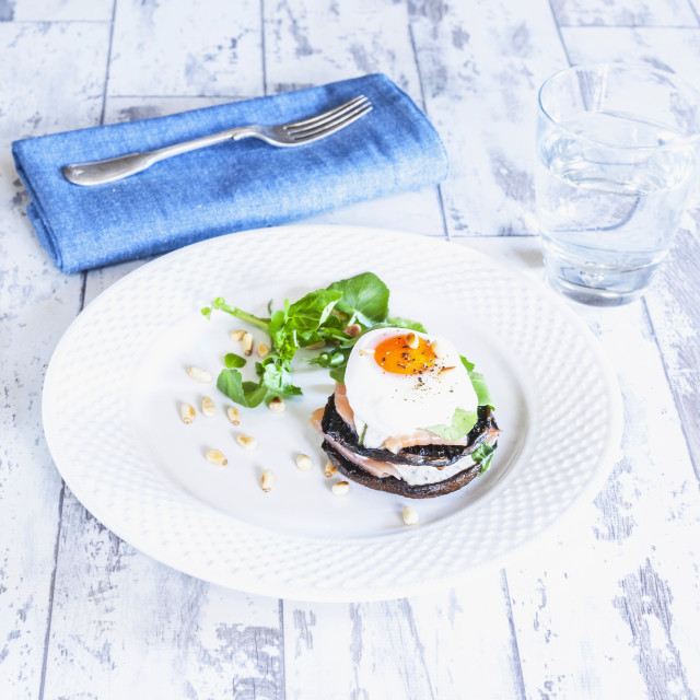 """A stack of poached egg and salmon on a mushroom with watercress"" stock image"