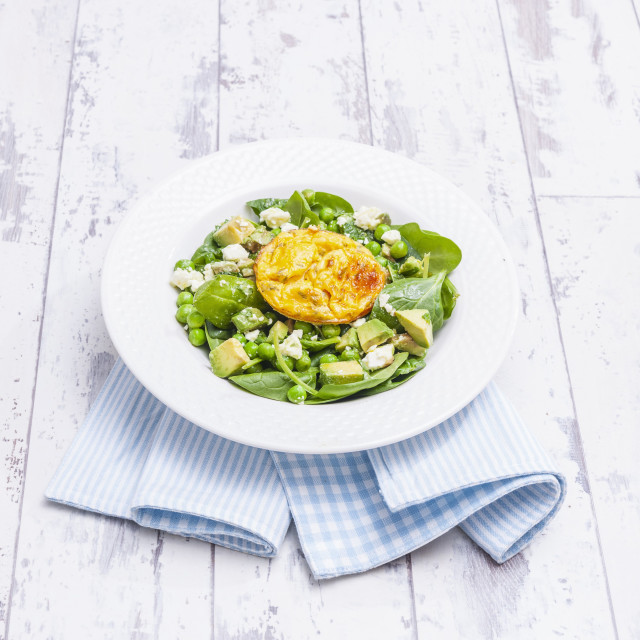 """Baked eggs on pea and mint salad with feta cheese (England)"" stock image"