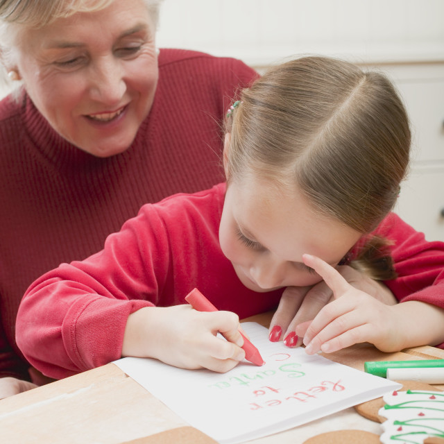 """Small girl with grandmother writing Christmas letter"" stock image"