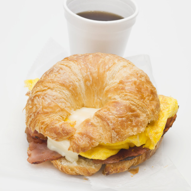"""Croissant with bacon, scrambled egg & cheese, cup of coffee"" stock image"