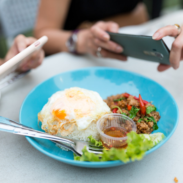 """""""Friends taking photo on thai food dishes before eating"""" stock image"""