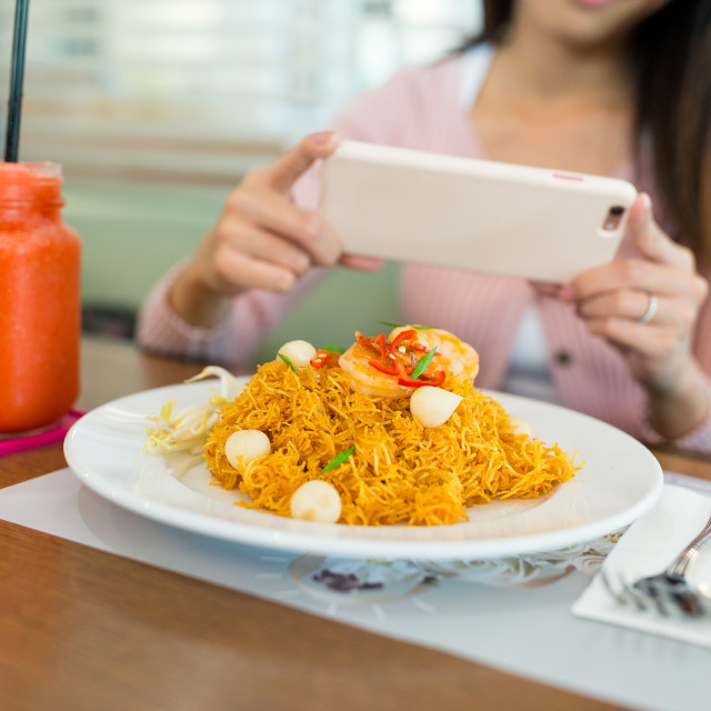 """""""Woman taking photo on fried noodles with cellphone"""" stock image"""