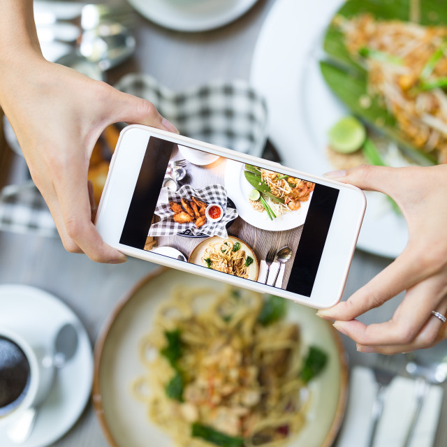 """""""Mobile phone taking photo on food from top in restaurant"""" stock image"""