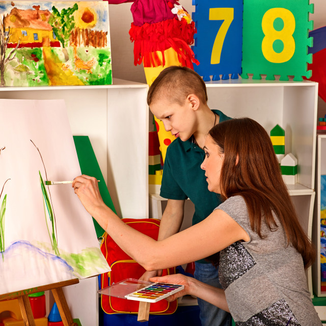 """""""Child painting finger on easel. Kid boy learn paint school."""" stock image"""