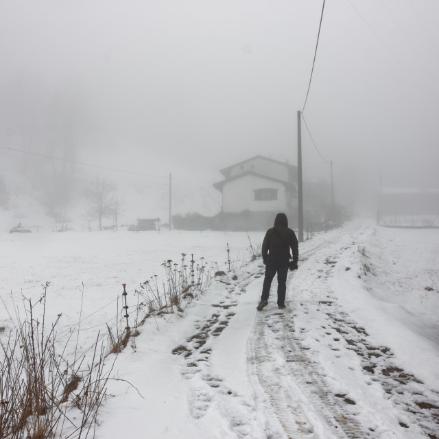 """Lonely man walking to home in the winter fog with snowy landscape"" stock image"