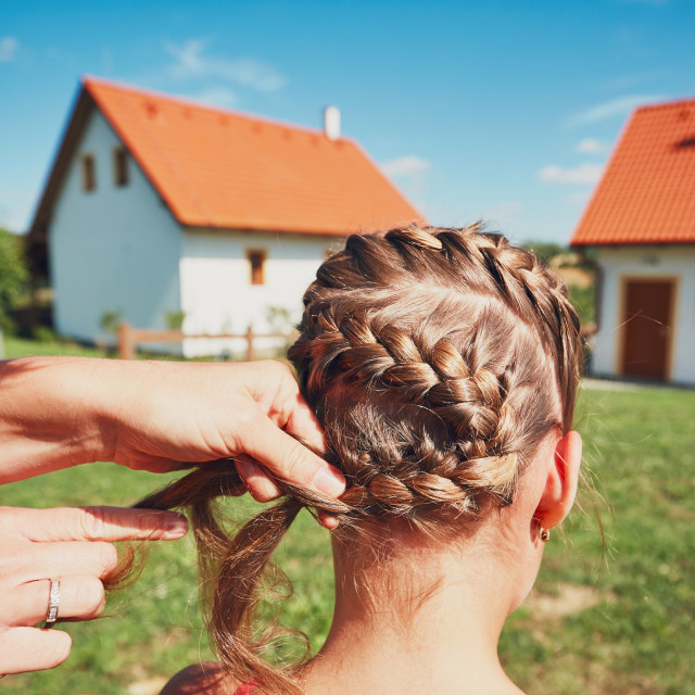 """""""Young woman making hair braids of the little girl on the garden in the countryside."""" stock image"""